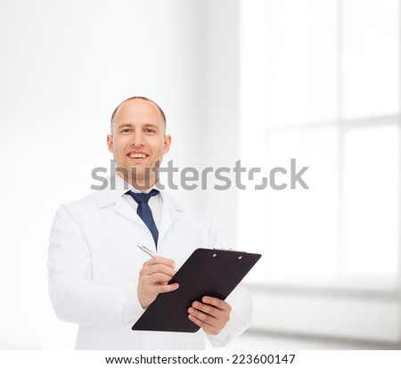 medicine, profession, workplace and healthcare concept - smiling male doctor with clipboard writing prescription over white room background - stock photo