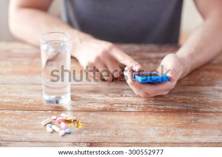 medicine, technology, nutritional supplements and people concept - close up of male hands smartphone, pills and water on table - stock photo