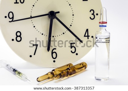 medicine vials and syringe, the clock shows the time of the medication - stock photo