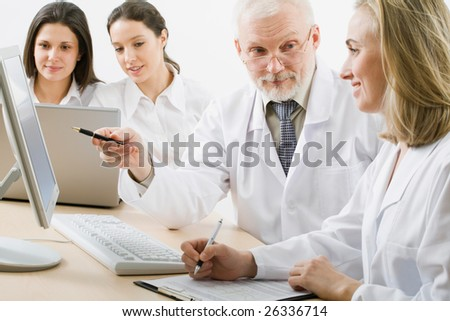 Medicine workers looking at monitor - stock photo