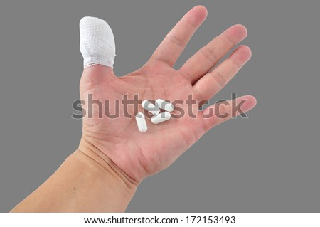 Medicines pill in hand with thumb bandage. - stock photo