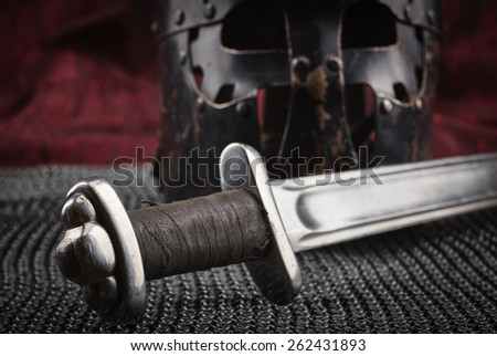 Medieval armour, helmet and sword, red canvas background - stock photo