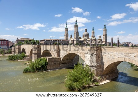 Medieval bridge and the Pillar Cathedral in Zaragoza, Aragon, Spain - stock photo