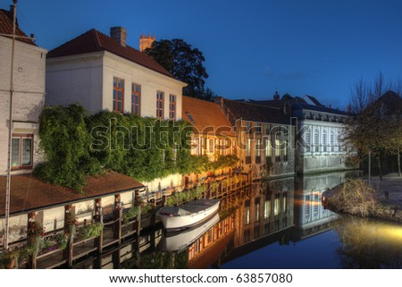 Medieval buildings along a canal in Bruges, Belgium, at night, with the famous Belfry just visible - stock photo
