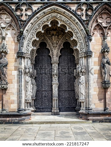 Medieval Cathedral doors surrounded by religious statues. United Kingdom, Europe. - stock photo