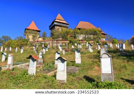 Medieval church surrounded by old cemetery from UNESCO world heritage list in Viscri village, Transylvania, Romania - stock photo