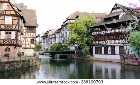 Medieval cityscape of Rhineland black and white timber-framed buildings in the Petite-France district alongside the river Ill on sunny summer day - France, Alsace region, Strasbourg - stock photo