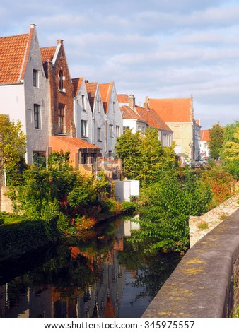 medieval houses along canal tourist destination Bruges Brugge Belgium Europe  - stock photo