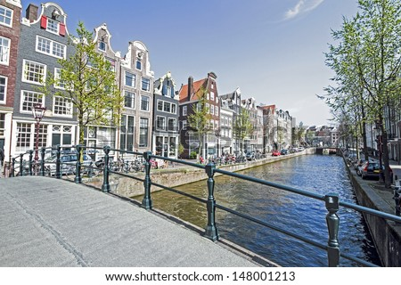 Medieval houses along the canal in Amsterdam Netherlands - stock photo