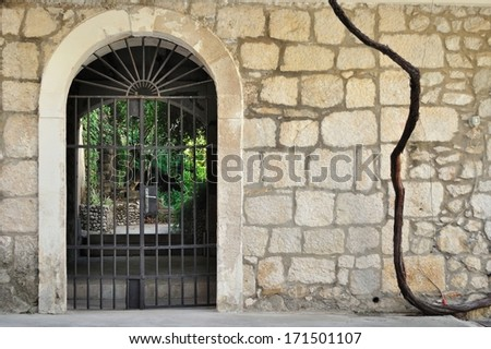 Medieval iron gate in ancient stone wall - stock photo