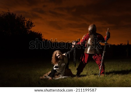 Medieval knight is going to make an execution of a witch. Night forest on the background. - stock photo