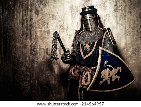 Medieval knight on golden wall background - stock photo