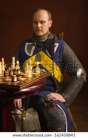 Medieval knight plays chess in a castle  - stock photo