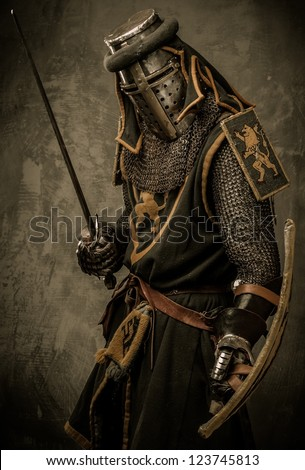 Medieval knight with sword and shield against stone wall - stock photo