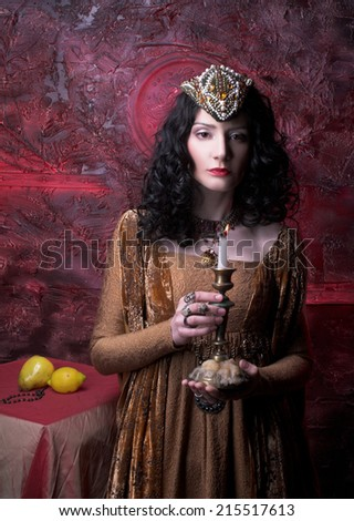 Medieval  lady. Portrait of young woman with dark curly hair in yellow dress. - stock photo