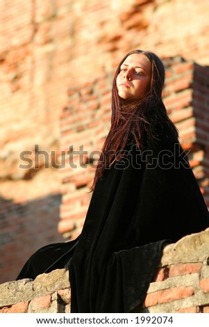 Medieval lady with black mantle for Halloween carnival - stock photo