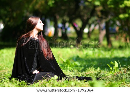 Medieval lady with black mantle on the grass for Halloween carnival - stock photo