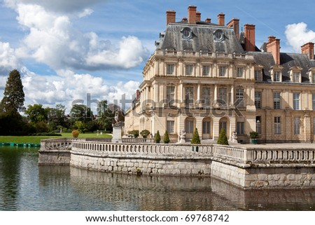Medieval landmark royal hunting castle Fontainbleau near Paris in France and lake with white swans - stock photo