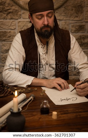 Medieval man sitting on a old table and sign a contract - stock photo
