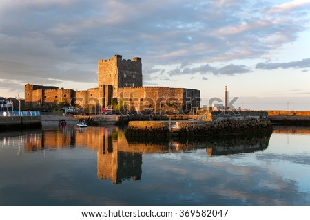 Medieval Norman Castle in Carrickfergus, Northern Ireland, and its reflection in water at sunset. - stock photo