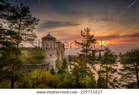 Medieval Olavinlinna fortress sunset view through trees. - stock photo