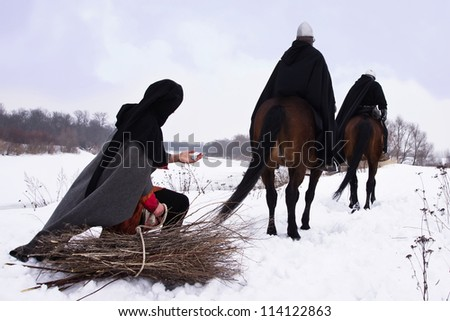 Medieval peasant with a firewood bundle and riding knights Hospitallers - stock photo