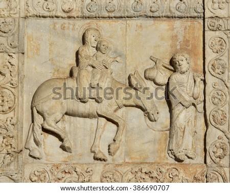 Medieval relief of Jesus flight ot Egypt with Virgin Mary and Saint Joseph, from Basilica of San Zeno facade, in Verona (12th century) - stock photo