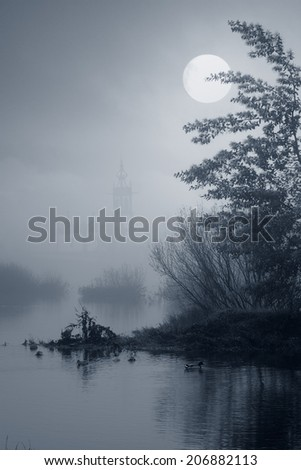 Medieval river city of Ponte de Lima, north of Portugal, in a foggy full moon night - stock photo