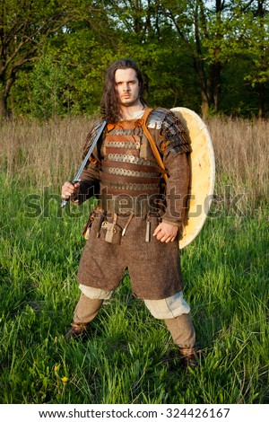 Medieval slav warrior man wearing in ancient armor with sword. - stock photo