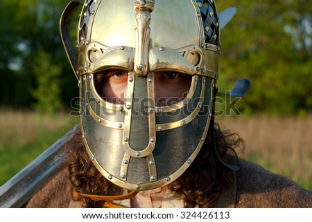Medieval slav warrior man wearing in ancient armor with sword and helmet. Close up detail. - stock photo