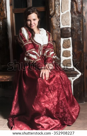 Medieval style portrait of attractive woman in red dress with wine glass in her hands - stock photo