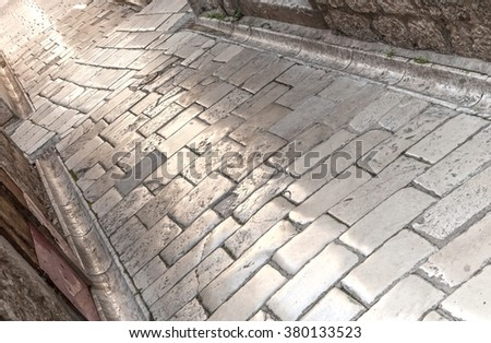 Medieval town street paved with stone slabs polished by milions of footsteps - stock photo