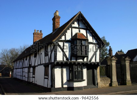 Medieval Tudor age long house of black beam timber and whitewash photographed against blue sky. Oxfordshire England - stock photo