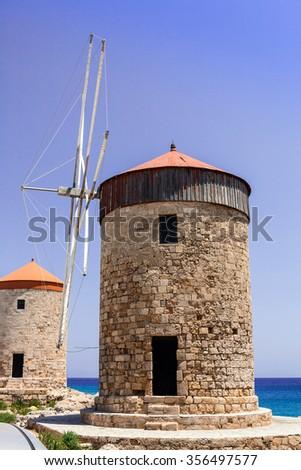 Medieval windmills at the Mandraki harbor in Rhodes. - stock photo