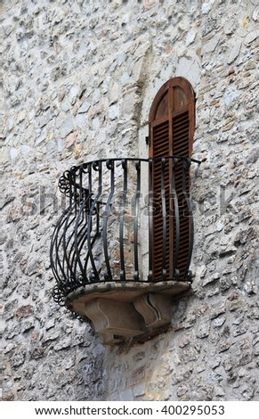 Medieval window and balcony with shutters closed - stock photo