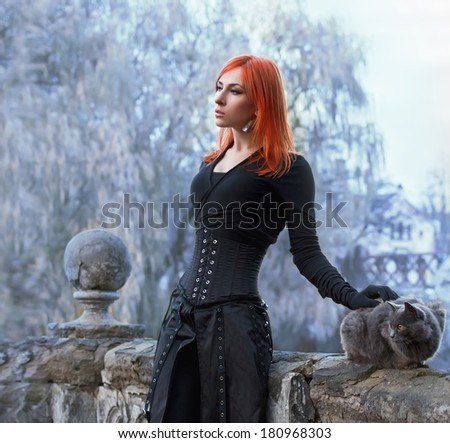 Medieval winter story with woman and cat - stock photo