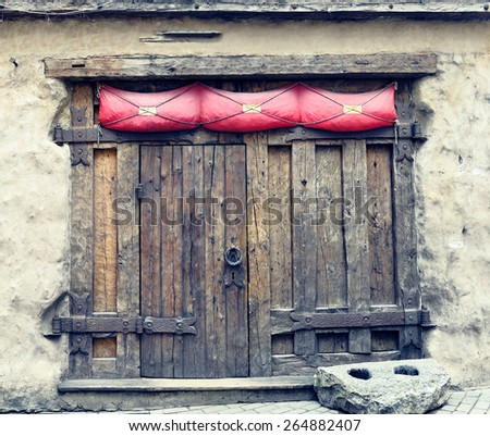 Medieval wooden gate with ancient metallic locker - stock photo
