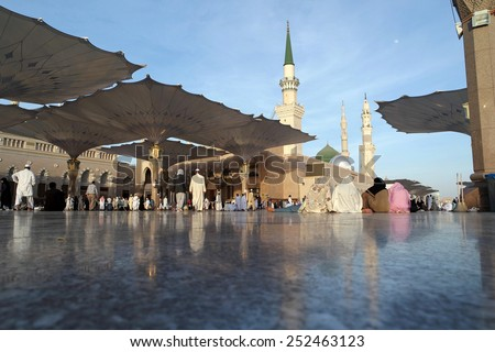 MEDINA, KINGDOM OF SAUDI ARABIA (KSA) - JAN 31: Women sitting in front of the mosque of the Prophet Muhammad on January 31, 2015 in Medina, KSA. Prophet's tomb is under the green dome. - stock photo
