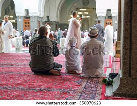MEDINA, SAUDI ARABIA - JANUARY 31 : Muslims pray inside Masjid Quba January 31, 2015 in Medina, Saudi Arabia. This is the first mosque built by Prophet Muhammad (pbuh) in Islam - stock photo