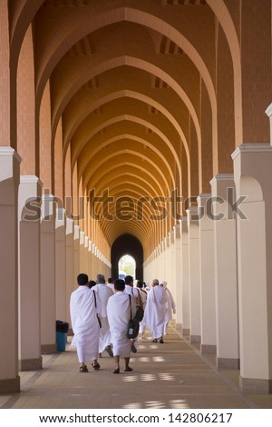 MEDINA, SAUDI ARABIA - JUN 1:Moslem pilgrims in 'ihram' cloth at a mosque on June 1, 2013 in Al Madinah. 'Ihram' clothes consist of two unhemmed white clothes intended to make everyone appear the same - stock photo