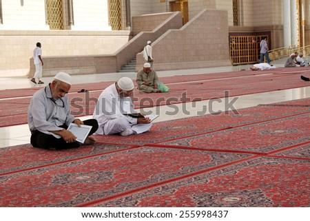 MEDINAH, SAUDI ARABIA - FEB 1: Muslims read Quran and pray inside of Masjid Nabawi Feb 1, 2015 in Medina, Saudi Arabia. Nabawi Mosque is the second holiest mosque in Islam. - stock photo