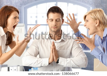 Meditating closed eye businessman in office with arguing colleagues shouting and fighting. - stock photo