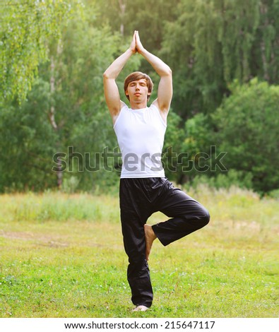 Meditating, fitness, yoga - concept, man doing exercise on the grass - stock photo