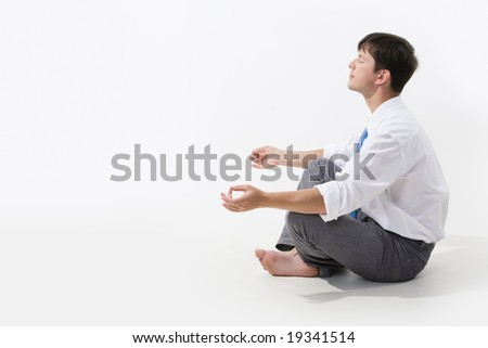 Meditating man sitting in pose of lotus in profile over white background - stock photo