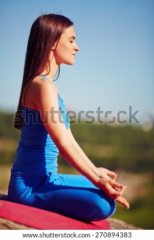 Meditating woman relaxing in pose of lotus outdoors - stock photo