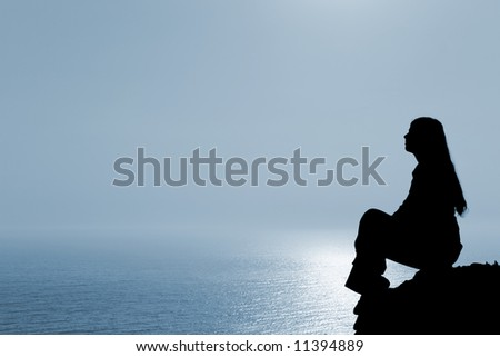 Meditating woman silhouette against seascape. - stock photo