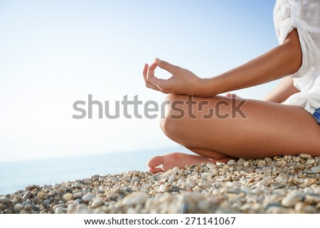 Meditation in lotus position on the beach. - stock photo