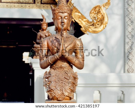 Meditation of Buddha in bronze metal. Sculpture past the entrance of a Thai temple in Chiang Mai  - stock photo