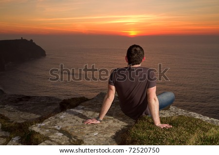 Meditation on Cliffs of Moher at sunset - stock photo