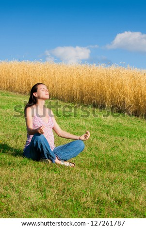 Meditation on summer day on green field with wheat in background. - stock photo